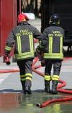 Пожарные носят трубы гидранта и шланга после положенное  Стоковая Фотография RF