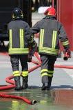 Пожарные носят трубы гидранта и шланга после положенное  Стоковое Изображение RF