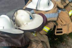 Пожарные одежды шлемов ` s пожарных на улице стоковые изображения
