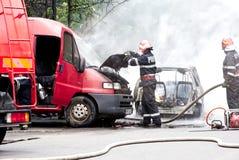 Пожарные поднимая клобук потушенный автомобиль стоковая фотография