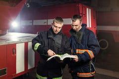 Пожарные пожарного в действии стоя около пожарной машины Eme Стоковое фото RF