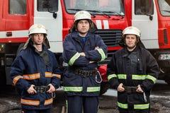Пожарные пожарного в действии стоя около пожарной машины Eme Стоковое Фото