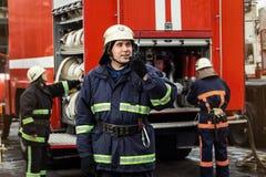 Пожарные пожарного в действии стоя около пожарной машины Eme Стоковые Изображения RF