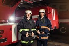 Пожарные пожарного в действии стоя около пожарной машины Eme Стоковое Изображение
