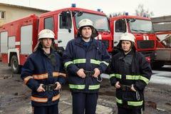 Пожарные пожарного в действии стоя около пожарной машины Eme Стоковая Фотография RF