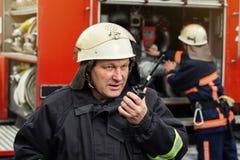 Пожарные пожарного в действии стоя около пожарной машины Eme Стоковые Изображения