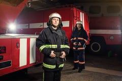 Пожарные пожарного в действии стоя около пожарной машины Eme Стоковая Фотография