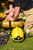 Пожарные подготавливают дыхательный аппарат на сцене огня Стоковые Изображения
