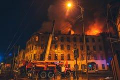 Пожарные с пожарным рукавом и пожарными машинами или тележками воюют огонь Огромный дым, горячее пламя в горящем доме стоковое изображение