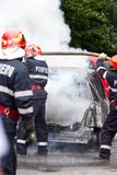Пожарные тушат автомобиль на огне стоковое фото rf
