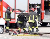 Пожарный в действии во время автомобильной катастрофы Стоковое фото RF