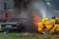 Пожарный используя воду и гаситель, пожарного используя воду и автомобиль гасителя на огне, стоковые фотографии rf