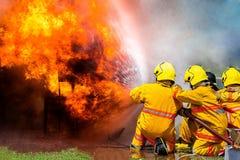 Пожарный используя воду и гаситель, пожарного используя воду и автомобиль гасителя на огне, стоковые изображения rf