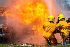 Пожарный используя воду и гаситель, пожарного используя воду и автомобиль гасителя на огне, стоковое фото