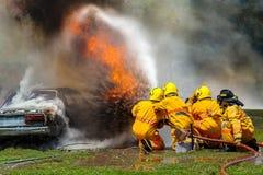 Пожарный используя воду и гаситель, пожарного используя воду и автомобиль гасителя на огне, стоковое изображение rf