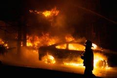 Пожарный идя пламенеющим автомобилем Стоковая Фотография