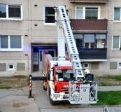 Пожарный начинает к uprise в телескопичную корзину заграждения пожарной машины, блока квартир в предпосылке Стоковая Фотография