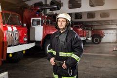 Пожарный пожарного в действии стоя около пожарной машины Emer Стоковое Изображение RF