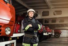 Пожарный пожарного в действии стоя около пожарной машины Emer Стоковые Изображения RF