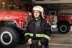 Пожарный пожарного в действии стоя около пожарной машины Emer Стоковая Фотография
