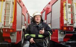 Пожарный пожарного в действии стоя около пожарной машины Emer Стоковые Фотографии RF