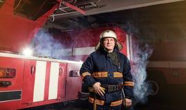 Пожарный пожарного в действии стоя около пожарной машины Emer Стоковое фото RF