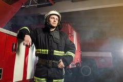 Пожарный пожарного в действии стоя около пожарной машины Emer Стоковое Фото