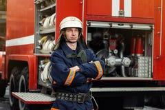 Пожарный пожарного в действии стоя около пожарной машины Emer Стоковое Изображение
