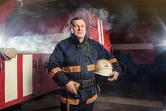 Пожарный пожарного в действии стоя около пожарной машины Emer Стоковая Фотография RF