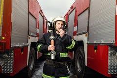 Пожарный пожарного в действии стоя около пожарной машины Emer Стоковые Фото