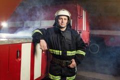 Пожарный пожарного в действии стоя около пожарной машины Emer Стоковые Изображения