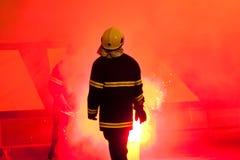 Пожарный стоя в дыме факела Стоковое Изображение
