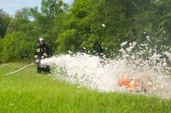 Пожарный тушит горящий куря пробел пункта автошины во время стоковое фото rf