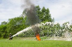 Пожарный тушит горящую куря автошину во время demonstrati стоковая фотография