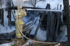 Пожарный тушит огонь Пожарный держа шланг с wat стоковая фотография