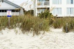 Пожалуйста держите с знака и пляжных домиков дюн Стоковые Изображения RF