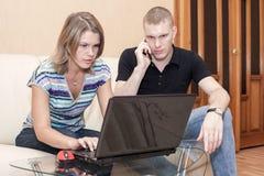 Пожененная пара несчастна с результатом для на-линии финансирования, человека вызывая банк с мобильным телефоном стоковые фото