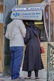 Пожененная пара разделяет наличные деньги на улице ATM, Kashan, Иране Стоковое Изображение RF