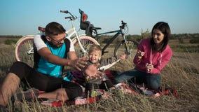 Пожененная пара с ребенком на предпосылке их велосипедов Пузыри и потеха мыла акции видеоматериалы