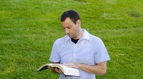 Пожененное чтение человека с его рукой на библии Стоковое Фото