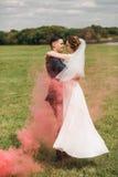 Пожененные милые танцы пар в красном дыме на луге Стоковые Изображения