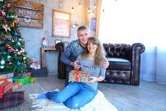 Пожененные пары держа подарки в руках, усмехаясь и обнимая каждое Стоковое Фото