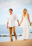 Пожененные пары, жених и невеста держа руки на заходе солнца на beaut Стоковые Фотографии RF
