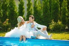 Пожененные пары около бассейна стоковая фотография rf