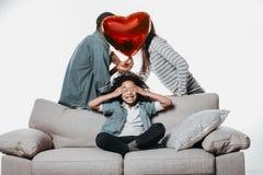 Пожененные пары целуя за воздушным шаром около ребенка Стоковые Изображения RF