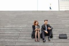 пожененные учителя дела пар используя таблетку и smartphon Стоковая Фотография