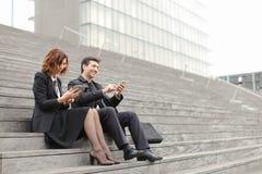 пожененные учителя дела пар используя таблетку и smartphon Стоковые Изображения