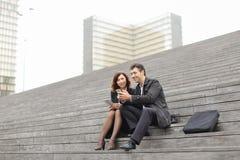 пожененные учителя дела пар используя таблетку и smartphon Стоковые Фото