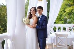 Пожененный детеныш соединяет как раз пожененный представлять на террасе, человек нежно обнимает его жену плечами стоковые изображения rf