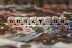 Пожертвование - куб с письмами, условиями участка денег - знак с деревянными кубами Стоковая Фотография